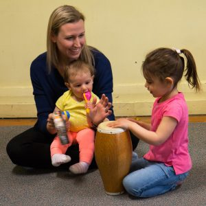 A mom and two kids learn to play the conga at a Rainbow Songs class