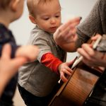 baby music class and teacher with guitar
